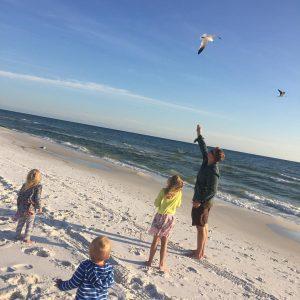 kids feeding seagulls on the beach in Destin