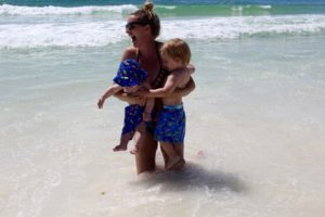 mom holding babies in the waves of the emerald coast, destin